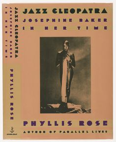 Book jacket design for Jazz Cleopatra. On orange-brown ground, a one-toned black photograph of the figure of Josephine Baker. She appears nude, holding her hands to her chest, with long chains of pearls wrapped around her hands and dangling down the length of her body. She also holds a length of fabric, possibly a dress. She wears makeup and large earrings and stands in an abstract rocky landscape. Stylized text above, below, and at the spine in black and purple. Doubleday colophon appears…