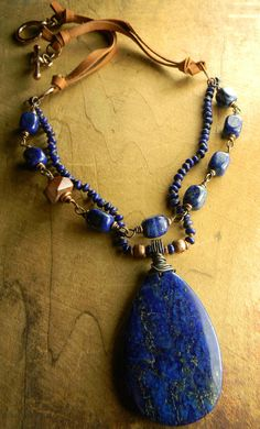 That simple necklace with punch! Lapis lazuli pendant wire wrapped with copper as the focal, surrounded with lapis lazuli rondelles knotted on Irish linen cord in a southwestern boho necklace design. The second strand is a rosary style arrangement of lapis nuggets (each bead wired and