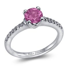 This white gold pink sapphire engagement ring features a round pink sapphire gemstone with round diamonds on the sides. Rothem Collection SKU: R0010PW
