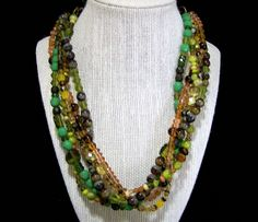 Vintage USA Artist handmade multi strand glass bead necklace Gorgeous assortment of faceted glass beads and art glass beads Shades of green, brown, and tan Transparent, opaque and swirled Sterling silver clasp, bordered by two large ovoid olive green beads 20 inches long Unsigned Very good condition, shows no wear to the beads I special in vintage beaded jewelry, please visit my store for more offerings International buyers welcome, over charges are refunded Priority shipping is optional…