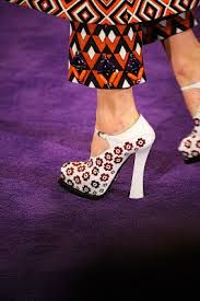 To extend the line, they wore platform shoes with the flare-heel profile evocative of the playful footwear that John Fluevog made for Deee-Lite's Lady Miss Kier, circa 1990, only these were lacquered with a contrast latex paint strip in a broad horizontal band. (One brief passage substituted mannish Oxford's with platform-crepe soles.) And the models each gripped vari-scaled satchels, doctor's bags, or the daintiest minaudière-scaled purses.