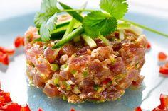 Recept voor: Tonijntartaar met Thaise smaken | 1. Snij de uitjes fijn (het witte deel + 2/3 van het groene deel). Doe in een schaal met de sambal, de vissaus, de koriander, olie en het limoensap. 2. Snij de tonijn met een mes heel fijn (zeker niet met de elektrische  …