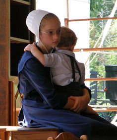 Amish girl holding her brother