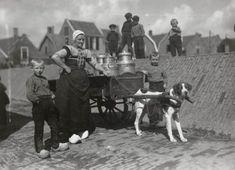 Vrouw en zes jongens in streekdracht, uit Bunschoten-Spakenburg. De groep poseert bij een hondenkar. Op de kar staan een paar melkbussen. De vrouw is gekleed in daagse of opknapdracht. De jongens dragen een klepbroek met een smalle klep, waaraan te zien is dat ze de vissersdracht dragen. Boeren droegen een klepbroek met een brede klep.  1918-1941 #Utrecht #Spakenburg