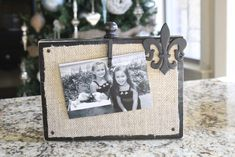 easy to make photo frame: piece of wood, black paint, spray glue, burlap, furniture nails, wood clip and wood embellishment!