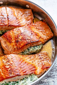 Creamy Spinach Stuffed Salmon in garlic butter is a new delicious way to enjoy salmon! Filled with cream cheese, spinach, parmesan cheese and garlic, this salmon beats anything found in a restaurant. A low carb salmon recipe that includes pan fried AND oven baked methods!