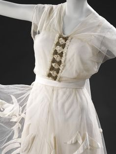 A full length evening dress of white organza and net with appliquéd stylised swallow motif across skirt. The sleeveless bodice fastens behind with a row of attached diamanté bow brooches and two long bands of tulle which fall to the floor.