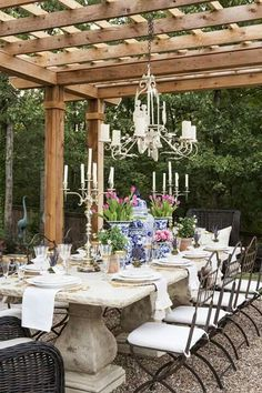 Whimsical garden features a French style concrete dining table seating eight wrought iron dining chairs with white cushions and two wicker host chairs illuminated by a chandelier hung from a pergola. Chandelier For Long Table French Country Dining Room, Modern French Country, French Country Decorating, French Country Porch, Country Patio, French Patio, Country Blue, Concrete Dining Table, Dining Room Table Decor