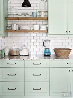 Light green cabinets soften this kitchen's hardworking edges. The pastel paint color brightens the space and reflects its shiny white subway tile backsplash while adding style that is equal parts modern and vintage. Paint Color:Benjamin Moore, Tea Light 471./