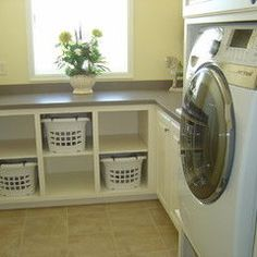 Laundry room with counter space to fold, cubies for folded laundry, cabinet space for detergent, and a sink for prewashing/handwashing.  All this needs is a tension rod for hang drying clothes and an enclosed trash bin.