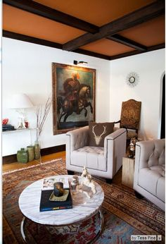 """""""I know what I like, but it doesn't necessarily have a rhyme or reason, or cohesive design plan behind it,"""" Zervas says. """"I appreciate a healthy mix and combining pieces from multiple periods — antiques with modern.""""  Chairs: Overstock.com; coffee table: CB2; pillows: Home Goods; painting: antique, Skinner Auction House"""