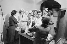 GUY'S HOSPITAL: LONDON, 1941. A group of nurses at Guy's Hospital in London get cups of tea from the canteen, poured for them buy members of the Women's Voluntary Service (WVS). There are different types of nurses at work at Guy's, including VADs (Voluntary Aid Detachment nurses) and those from the Red Cross.