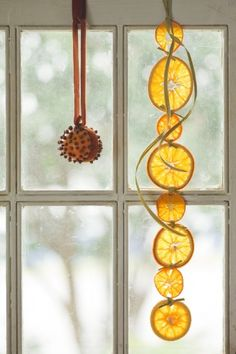 Hang orange garlands in a window where the light can shine through ...