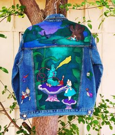 Custom hand painted Disney's Alice in Wonderland denim jacket with caterpillar smoking hookah, white rabbit, tea cup, drink me bottle and mad hatter hat on back and cheshire cat on front by @bleudoor on Instagram