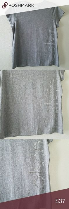 5a07a074184 Calvin Klein T-shirt Beautiful brand new with tag Calvin Klein t-shirt with  silver tone embellishment. Approx length of t-shirt Front armpit to armpit  ...