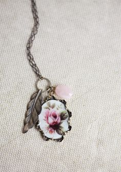 "Garden View Indie Pendant Necklace 39.99 at shopruche.com. Vintage-inspired floral and feather pendants and a shimmering pink stone render this brass necklace the perfect transitional piece for day to night.32"" long, Pendants: 3"" long"