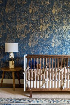 Eclectic boy's nursery features a wall clad in blue and gold print wallpaper lined with a mid century modern crib next to a tripod accent table topped with a painted driftwood and rope lamp alongside a blue kilim rug layered atop a cream wool rug.