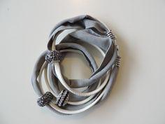 Bracciale in eco-pelle bianca e fettuccia grigia, a tre giri di polso, con charm grigi e binco-nero. Chiusura con calamita color argento.