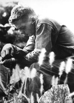 A young Marine holding rosary beads while solemnly bowing his head in prayer for the safety of him and his comrades, shortly before the 1st Marine Division launched an offensive against entrenched communist troops during the Korean War. Korea, 1951.