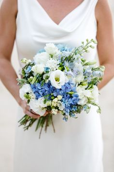 Country style bouquet consiting of blue delphinium and hydrangea and white lisianthus.