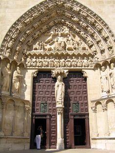 En la fachada sur, Plaza del Rey San Fernando, Puerta del Sarmental (1235), de estilo gótico. La puerta queda dividida por un parteluz en donde luce una estatua moderna (la original se encontraba muy deteriorada) representando al Obispo don Mauricio - también podía ser el obispo don Asterio de Oca o San Indalecio -. En las jambas aparecen esculpidas seis figuras, cuatro de ellas representan a Moisés, Aarón, San Pedro y San Pablo. En el tímpano la figura de Jesucristo Majestad, flanqueado por…