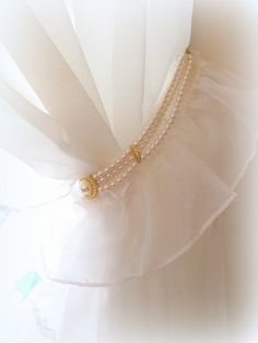 Curtain tie-back, adorned with old jewelry