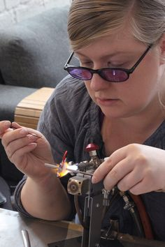 Glass artist Marja Hepo-aho making a small glass bird sculpture with lampworking technique.