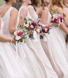 Early Spring Wedding // Pink  | Bridesmaids in long ivory dresses carry pretty bouquets in shades of pink, tied with white ribbons.     Venue: On Sunny Slope Farm | Photographer: The Mallorys