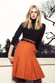 "{ Teacher Style } ""fall"" Orange pleated a-line skirt, black belt, black long sleeve boatneck top, black booties or flats."