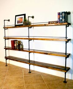 This industrial pipe shelving includes a bottle stop bar. This is great for library shelving or to hold alcohol. This shelving concept was originally purchased by Marriott Hotels for their shipping container bar. The goal of this piece was to be used as above-bar shelving and includes a removable bottle stop. This industrial bookcase is also great for home offices.  The pipe shown is featured in Gunmetal, and the wood shelves pictured are beautiful knotty pine in a custom Medium Walnut stain…