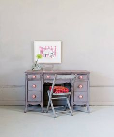 diminuitive desk in a lavendar grey shade with oversized pink knobs.  love the pairing of a folding chair painted in an off shade of grey
