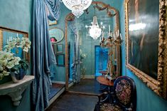 An eccentric English hallway in turquoise with turquoise drapes and large orante gold gilt framed mirrors and paintings. Brass candelabra and crystal chandelier, beautiful mix of classical and gothic styles. Grade1 listed country estate in Oxfordshire via http://www.airspaces.co.uk/locations/english-eccentric/