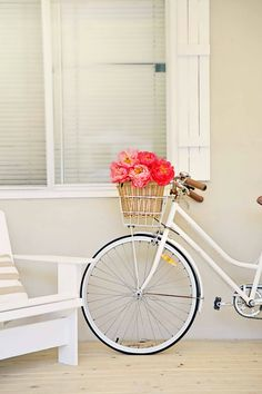 Vintage white bike with a basket full of flowers on the porch - perfect!