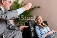 Male Therapist Using Hypnosis Therapy On Young Woman stock photo | iStock
