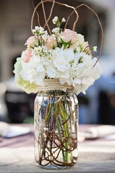 large jar filled with fresh flowers, branches and wrapped with rope for centerpieces