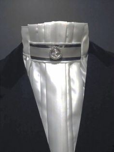 White pleated Euro-style stock with charcoal grey/light silver and diamante tab.  Made by Equestrian Pzazz in New Zealand $55.00 Please visit our page for more stunning and unique designs: https://www.facebook.com/eqpzazz