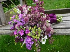 A wild-looking bouquet of lilac, honesty, blossom and wild flowers.