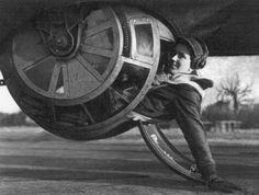 S/Sgt. Alan E. Magee poses for the camera, halfway into the tight confines of the ball turret of a B-17 Flying Fortres