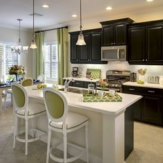 Dark cabinets contrast with lime green and white in this beautiful kitchen at the White Sand 2 model home in the Eagle Trace community. Contact us to see how we can make your dream a reality!