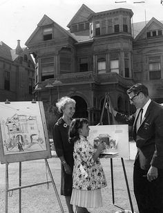 Leo Politi in front of the Castle working on his 1964 book, Bunker Hill, Los Angeles, with nine-year-old Susan Marshall and county librarian Mary Rogers Smith. L.A. Public Library