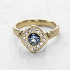 Discover the beauty of a Montana Sapphire Ring. An unconventional take on a classic halo...Our Helena ring is both luxe & modern. A radiant Montana Mountain Teal Sapphire center stone is surrounded by a sea of diamonds.