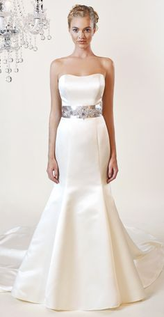 This gown is adorned with beaded belt at natural waist, with clean lines and chapel length train.