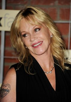 Melanie Griffith's strawberry blonde locks shine in the spotlight. Mrs. Antonio Banderas keeps her medium-length hair styled with loose waves and face-framing bangs.