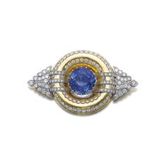 Sapphire and diamond brooch Set with a circular-cut sapphire weighing 26.38 carats, within a frame set with brilliant-cut diamonds, the sides of palmette design similarly set.