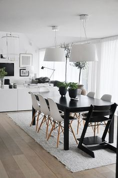 Wide grey toned wooden flooring, textured grey rectangular rug, black table, white chairs, black baby seat, white lighting
