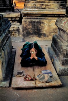 Steve McCurry, INDIA. Bodhgaya. 2000. A devotee prostrates at a prayer festival. Such prayers often last for many hours.