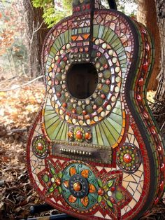 Mosaic guitar. Made with beautiful hand painted art glass, stained glass, freshwater pearls, Carrolton glass tiles, iridium glass tile, glass beads, mirrored glass, pebbles, glass cabochons, vitreous glass tile, and iridescent glass beads. I added a painted metal flower design with a vintage watch face to give it whimsy. The turn pegs are made from copper patined soldering wire.