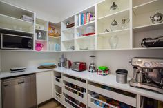 This very functional butler's pantry features dishwasher, fridge large bench space for appliances and shelving above and Blum tandembox pull out drawers below