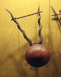 AFRICAN HONR LYRE Uganda or Kenya; century Decorative lyre made with gourd body and antelope horn arms. The rim of the gourd is decorated with bristles. Lyres have two wood or horn arms that project from the body African Vacation, Antelope Horns, African Textiles, Coconut Shell, Gourd Art, World Music, Harp, What Is Like, African Art