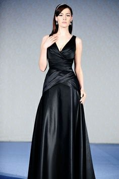 Floor-length A-line gown in European Matte Satin with a cross-over pleated V-shaped neckline and asymmetrically draped empire waist and body